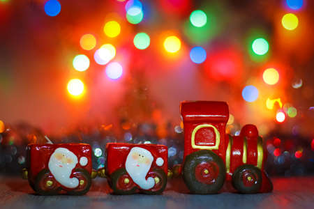Happy New Year background for greeting card.  Toy Steam Train with Santa Claus on a background of golden garlands and blur of colored lights.