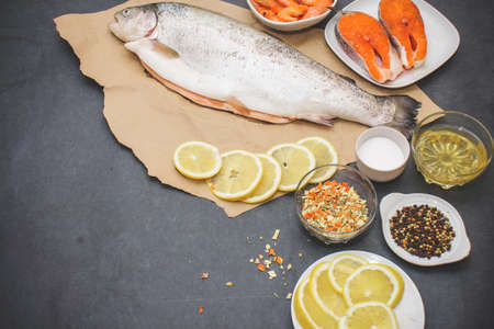 Raw fish with seasonings. On a dark gray tabletop lies a fish in Kraft brown paper with as much as a million pepper salt and a glass of buttered salmon and shrimp steaks. Stock Photo