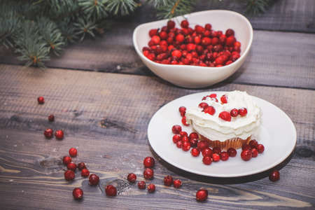 Festive composition for the background of New Year's postcards. Freshly baked cake on a white plate decorated with red berries and whipped white cream with a plate topped with red berries decorated with spruce sprigs on a light wooden table top. Stock Photo
