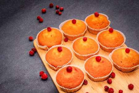On gray craft paper there is a wooden cutting board on which are freshly baked muffins decorated with red berries scattered on paper. Stock Photo