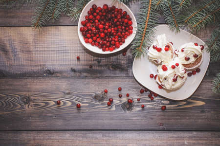 Freshly baked cake on a white plate decorated with red berries and whipped white cream with a plate topped with red berries decorated with spruce sprigs on a light wooden table top. Stock Photo