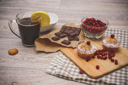 On a light wooden tabletop on a linen napkin napkin, there is a cutting board with two muffins, a broken chocolate bar and bright red berries in a small tree, next to a bowl with cookies. Festive pastry composition.
