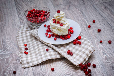 On a light tabletop on a linen napkin in a saucer cake with whipped cream with fresh berries, a bowl with red berries. Festive pastry composition.