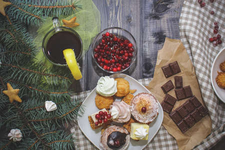 Close-up of sweets on a white plate: coconut biscuit, pastila, meringue, cream roses, Turkish delight, next to a broken chocolate bar on craft paper, in a bowl sesame biscuits in a bowl on a checkered linen napkin, fresh red cranberries, a glass of dark drink decorated with a slice of lemon, some spruce branches. Festive pastry composition.
