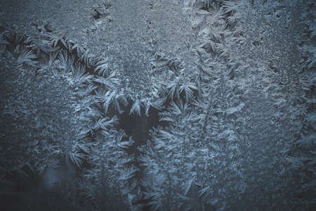 texture of frost and ice on glass as a pattern and ornament of a winter cold.glass painted with bizarre frost patterns window texture on a frosty day