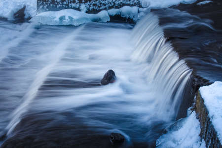 rapids of a waterfall, taken with a long exposure from a tripod in winter with islands of ice and snow. the photo of the winter forest in cold tones Stock fotó