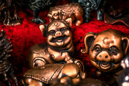 old market counter Buddhist figurines and masks of mythological characters in gold and bronze on a burgundy with a red background Stock fotó