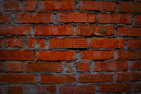 Bright red brick wall with light gray streaks of cement. brick wall background Фото со стока