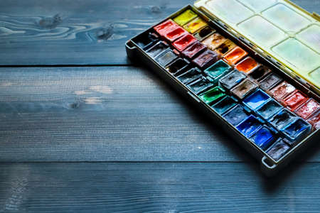 On a dark gray wooden tabletop, juicy watercolor paints, which the artist already used, are open.