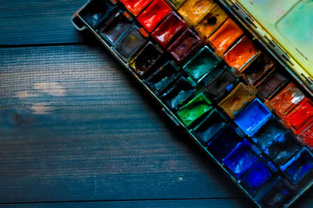 On a dark gray wooden tabletop, juicy watercolor paints, which the artist already used, are open. Wooden paint table many different colors watercolor.