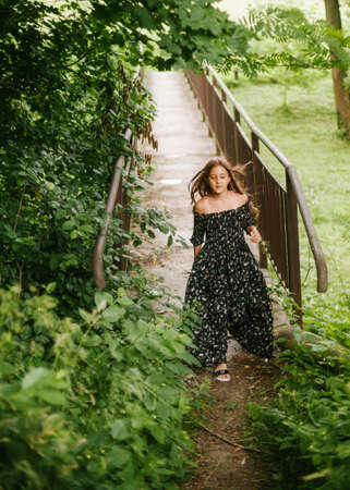 A girl in a beautiful black dress runs across a bridge in the park. Image with selective focus.