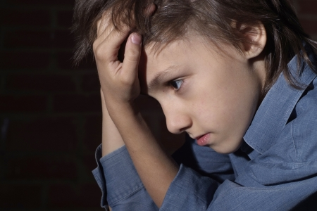 maltrato infantil: Niño caucásico frustrado sentado Foto de archivo