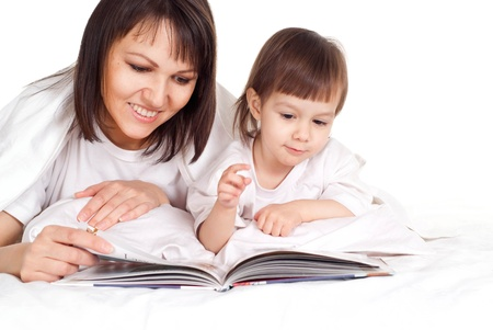 designer baby: A beautiful pretty Caucasian mother with her daughter lying on the bed with a book
