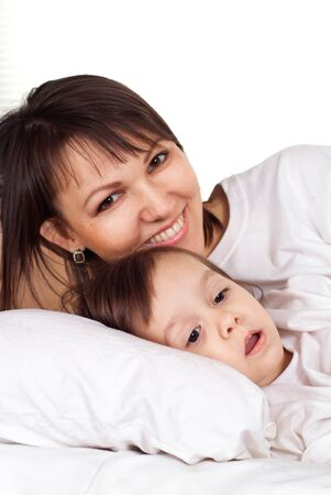 designer baby: A beautiful pretty caucasian mother with her daughter lying on the bed Stock Photo