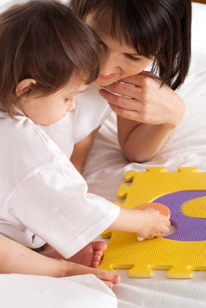 designer baby: A beautiful mother with her daughter play with a mat in the bed