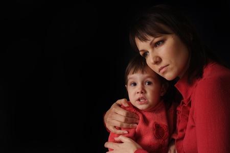 mujer llorando: Una mamá muy blanca, con una hija llorando triste sobre un fondo oscuro