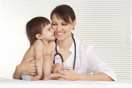 smiling doctor: Pediatrician doctor with little girl in her office Stock Photo