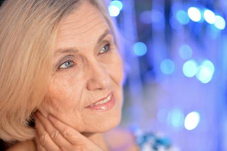 Cheerful elder woman on a blue background