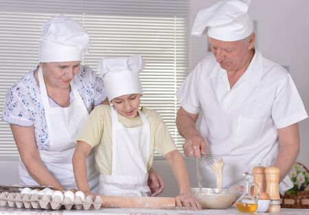 knead: An elderly couple and their grandson knead the dough for the pie together Stock Photo