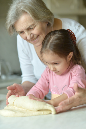 little dough: Little girl kneading dough with grandmother at the kitchen