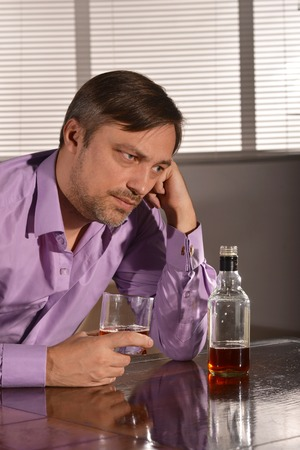 boozer: Cute and sad young man drinks whiskey at table Stock Photo
