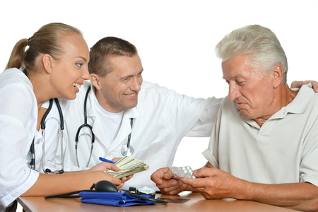 patient's history: Old man talking with two doctors Stock Photo