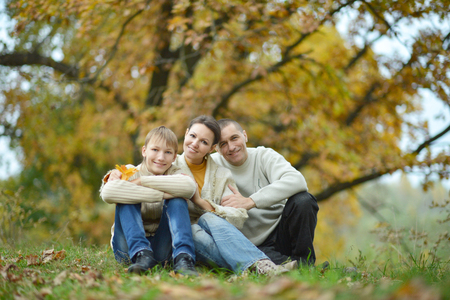 mam: Happy family in park sitting on yellow leaves Stock Photo