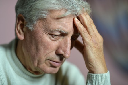 lamentable: Elderly man thinking about problems on a black background
