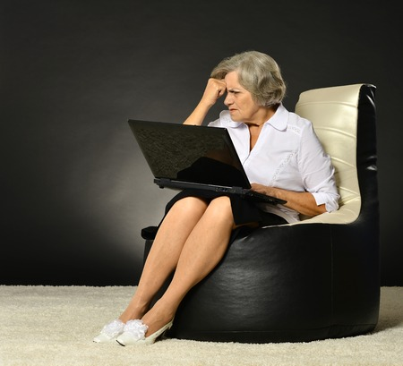 business cloth: Smiling old woman sitting in business cloth on dark background with laptop