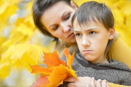 mam: Beautiful mother with a boy on a walk during the fall of the leaves in the park