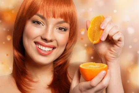 sidelong: Redhead girl holding orange on bokeh background