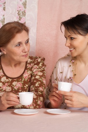 yearning: older woman with her adult daughter on a pink background