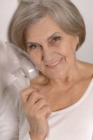 inhalation: Close-up portrait of an elderly woman making inhalation