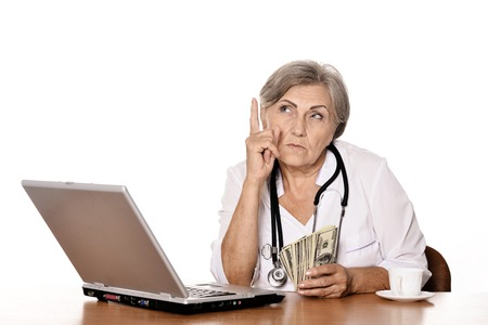 doctor with dollars: Thoughtful senior doctor sitting at table with laptop and holding dollars