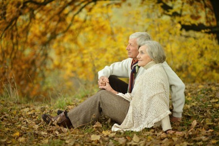 Happy elderly couple sitting in autumn nature