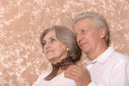 Close-up portrait of a sad elder couple on brown background