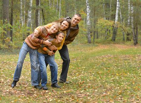 familia abrazo: Familia de cuatro pasar tiempo en el bosque de otoño