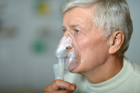 inhalation: Close-up portrait of an elder man making inhalation