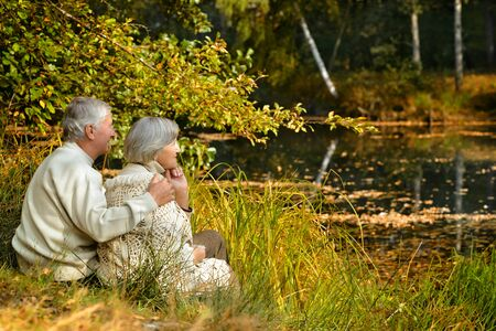 worried woman: old couple spending time outdoor in the park
