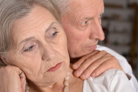 lamentable: Close-up portrait of a sad elder couple on white background