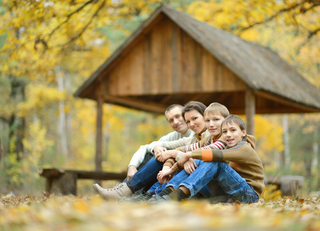sitting on the ground: Family of four sitting on ground in autumn forest