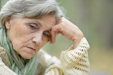 mirada triste: Pensativo mujer de edad avanzada en el fondo de las hojas de otoño