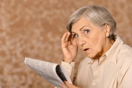 Portrait of aged surprised woman is reading newspaper Stock Photo