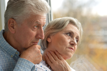 lamentable: Close-up portrait of a sad elder couple at home