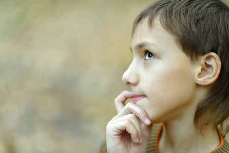 lamentable: Portrait of thinking young boy in park