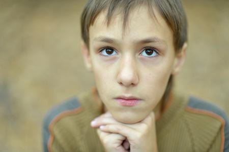 lamentable: Portrait of a sad boy outdoors in autumn Stock Photo