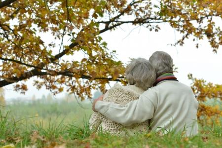 ancianos caminando: Pareja madura romántica está sentado en el parque en otoño Foto de archivo