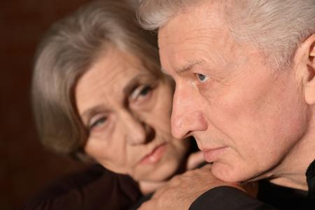 lamentable: Close-up portrait of sad elder couple on a black background