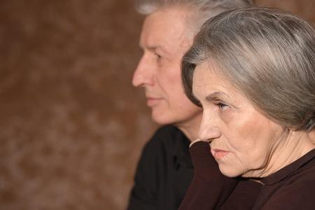 Close-up portrait of sad elder couple on a black background