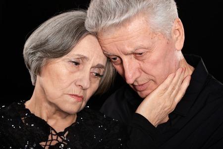 dolorous: Close-up portrait of sad elder couple on a black background